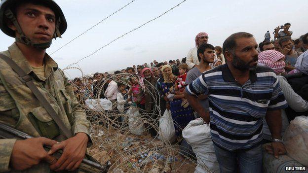 Turkish soldier monitors Kurdish refugees near border town of Suruc. 26 Sept 2014