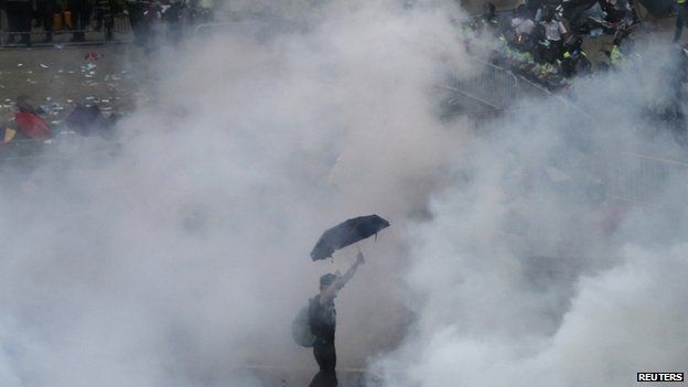 A protester walks in tear gas fired by riot policemen after thousands of protesters blocking the main street to the financial district outside the government HQ in Hong Kong on 28 September 2014.