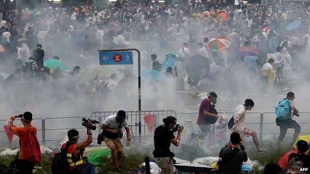 People disperse after police fired tear gas upon pro-democracy demonstrators near the Hong Kong government headquarters on 28 September 2014.