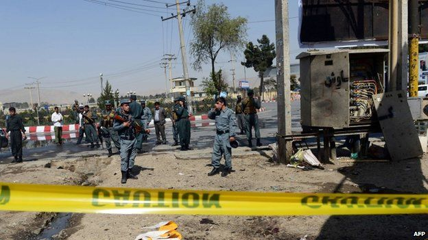 Afghan policemen stand guard at the site of a suicide attack near the international airport in Kabul on September 29, 2014.