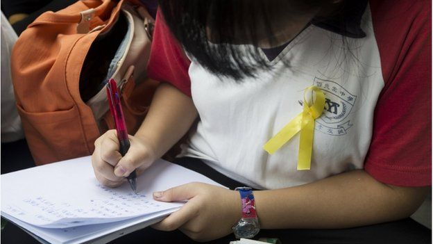 A secondary school student wearing a yellow ribbon attends a lesson conducted by her teacher during a rally outside government headquarters in Hong Kong