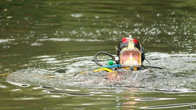 Police divers search the Grand Union Canal