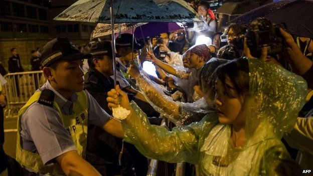 """Protesters shield police from the rain in Hong Kong's """"umbrella revolution"""""""