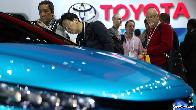 Attendees look at the Toyota FCV fuel cell vehicle concept car at the International CES at the Las Vegas Convention Center on January 7, 2014