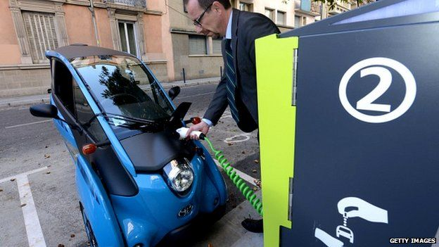 A man charging his I-Road Toyota electric car in Grenoble, France, Sept 2014