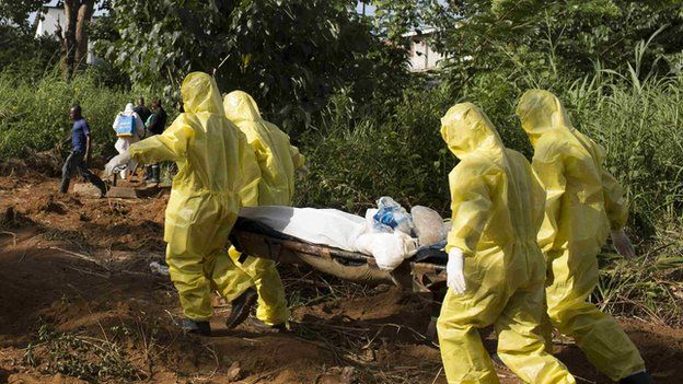 A burial team wearing protective clothing prepare the body of a person suspected to have died of the Ebola virus for interment, in Freetown September 28, 2014