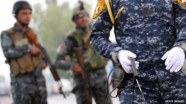 An Iraqi policeman holding a fake bomb detector