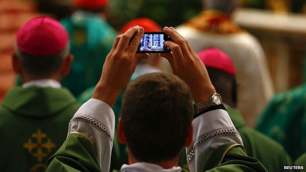 A priest takes a picture as Pope Francis celebrates a Mass to mark the opening of the synod on the family in Saint Peter's Square at the Vatican October 5 2014