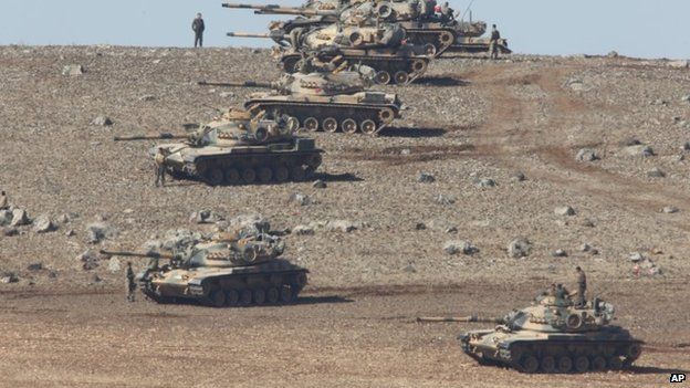 Turkish soldiers with tanks hold their positions on a hilltop in the outskirts of Suruc, at the Turkey-Syria border
