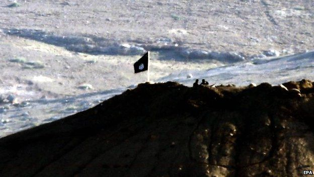 The view of an IS flag from the Turkish side of the border near Kobane, 6 Oct