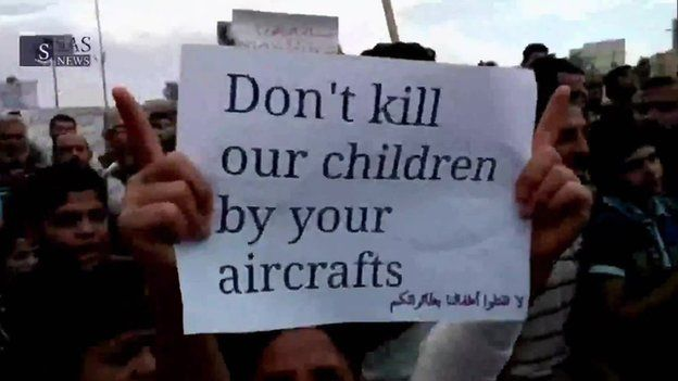 A protester waves a sign saying 'Don't kill our children by your aircraft'