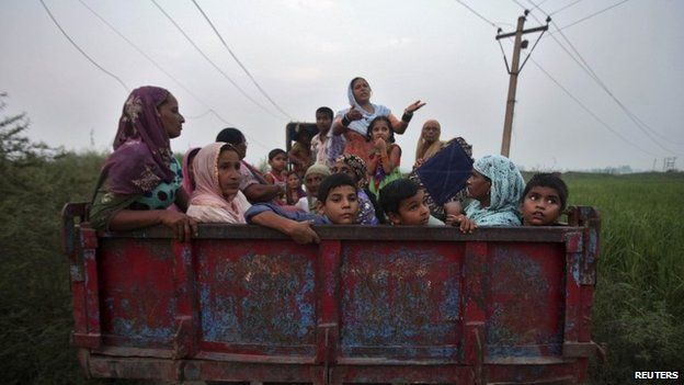 Indian villagers sit in a tractor trolley as they move to safer places at Devi Garh village near Jammu October 7, 2014.