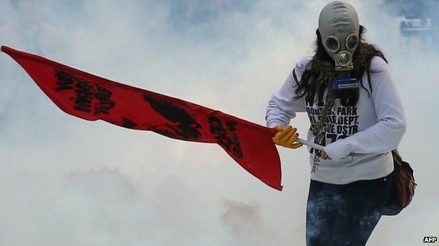 A protester holds a flag as police use tear gas and water cannon in Ankara against demonstrators who are opposed to what they say is Turkish inaction over the IS advance on Kobane (7 October 2014)