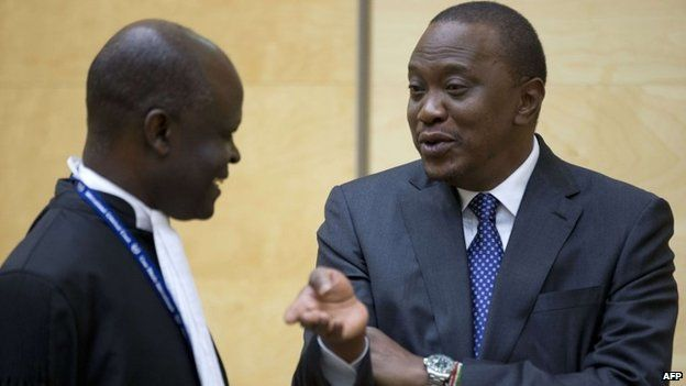 Kenya's president Uhuru Kenyatta talks to a member of his defence team at the International Criminal Court in The Netherlands on 8 October 2014
