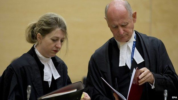 Uhuru Kenyatta's defence lawyers, Steven Kay and Gillian Higgins, look into legal documents at the International Criminal Court in The Netherlands on 8 October 2014