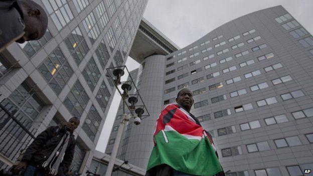 A supporter of Kenya's president Uhuru Kenyatta waits outside the International Criminal Court in The Netherlands on 8 October 2014