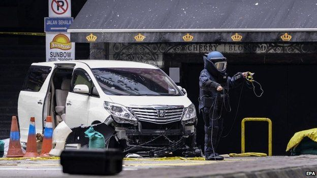 A member of a Malaysian bomb squad unit investigates the scene where a grenade exploded in Kuala Lumpur, Malaysia, on 9 October 2014