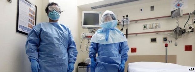 Bellevue Hospital nurse Belkys Fortune, left, and Teressa Celia, Associate Director of Infection Prevention and Control, pose in protective suits in an isolation room, in the Emergency Room of the hospital, during a demonstration of procedures for possible Ebola patients