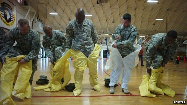 US soldiers from the 101st Airborne Division (Air Assault) - earmarked for the fight against Ebola - put on protective suits during training before their deployment to West Africa, at Fort Campbell, Kentucky (9 October 2014)