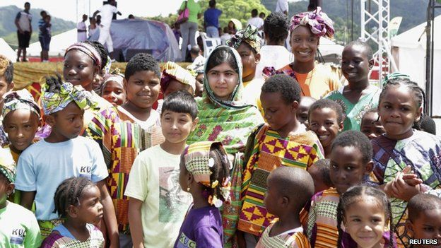 """Pakistani schoolgirl activist Malala Yousafzai poses for a photo with children attending a workshop, during her visit to the Emancipation Village at Queen""""s Park Savannah, in Port of Spain"""