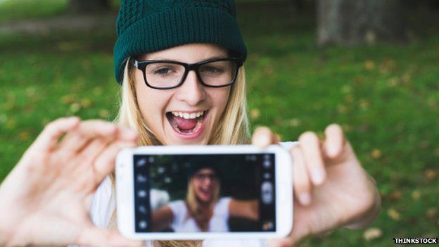 Girl in a hat and glasses grinning for a selfie