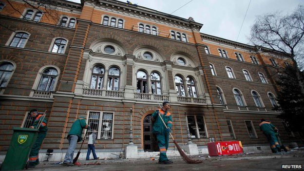People clean up after protests at government buildings in Sariajevo