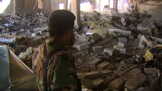 A Kurdish fighter stands amidst debris at the Rabia hospital