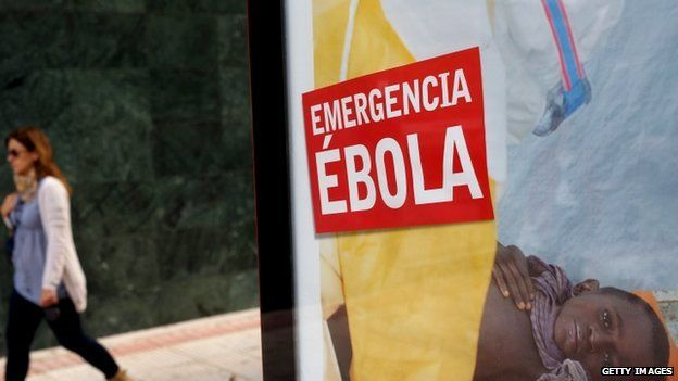 """A woman walks past a bus stop banner reading """"Emergency Ebola"""" near Madrid, Spain. Photo: 9 October 2014"""