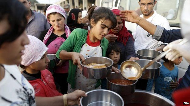 Syrian refugees who fled from Syrian Kobane, try to get food at a refugee camp at Suruc district, Sanliurfa, Turkey, 12 October 2014