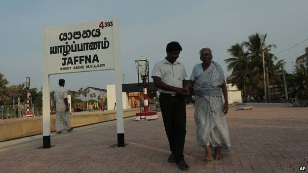 An elderly Sri Lankan ethnic Tamil woman is helped by a man as they walk along a platform at the Jaffna railway station in Sri Lanka, 12 October 2014