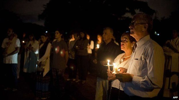 People participate in a candlelight vigil against violence in Cali on 8 October, 2014