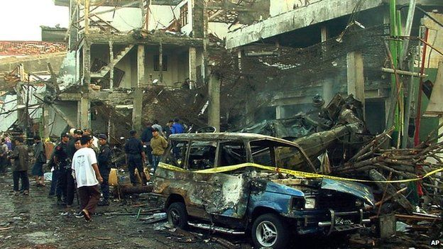 Police officers inspect a bombed nightclub in Denpasar, Bali, Indonesia, on 13 October 2002