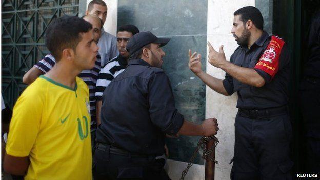 Hamas policeman talks to Hamas employees waiting to get their salaries at a bank in Gaza City (11/09/14)