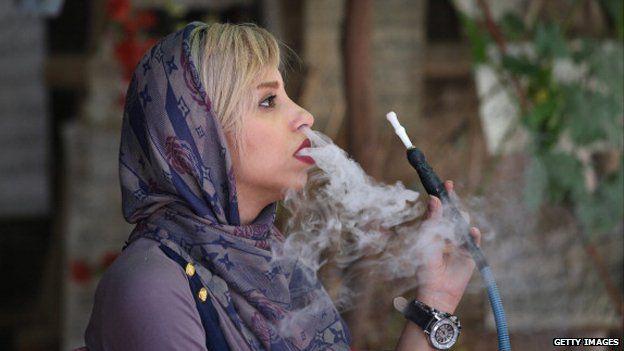 A woman smokes a hookah in Shiraz