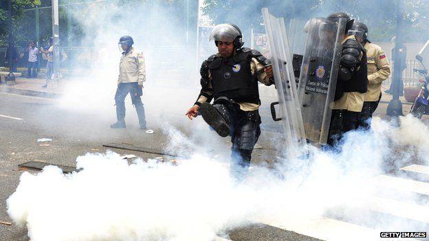 A policeman kicks away a tear gas canister in Caracas, May 2014