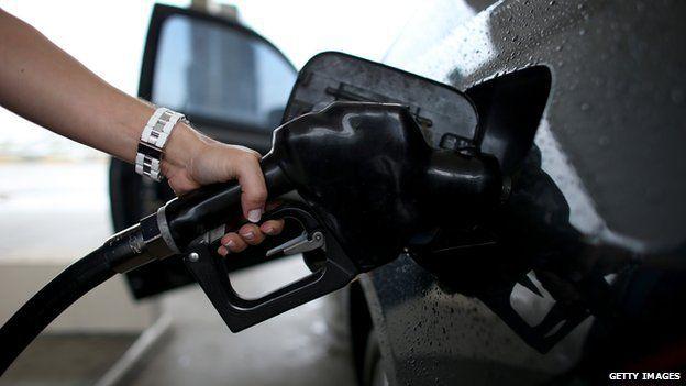 A woman pumps petrol into her car.