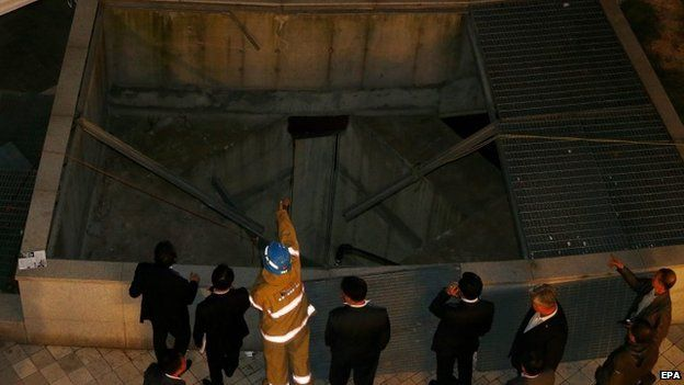 Officials inspect the collapsed ventilation grate in Seongnam City, South Korea on 17 October 2014.