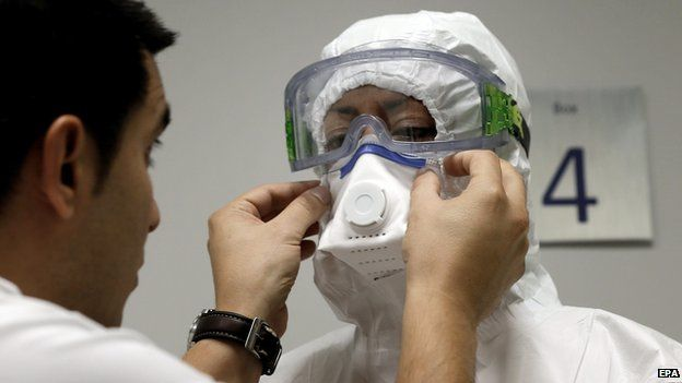Woman having mask and protective clothing fitted
