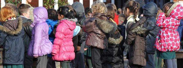 Schoolchildren lining up in a playground