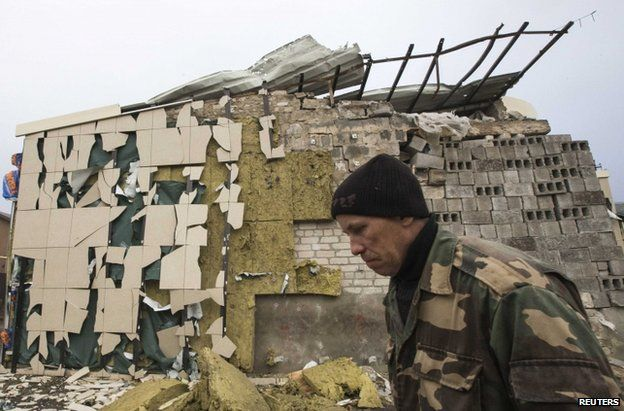 A man passes a cafe destroyed by shelling in Spartak, on the outskirts of Donetsk, 21 October
