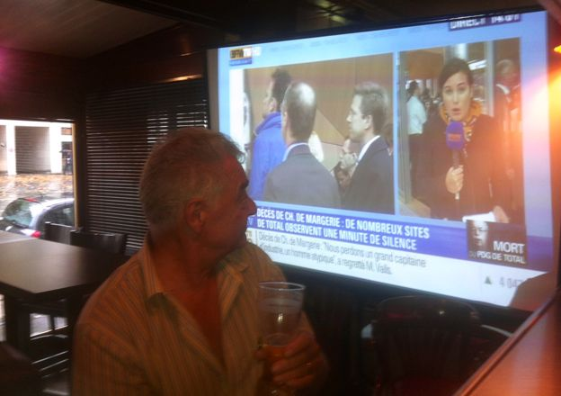 A man in a bar with BFMTV on the television screen in the background