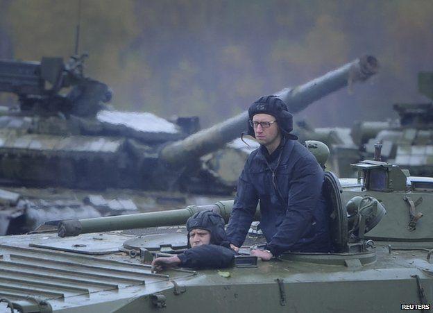 Ukrainian Prime Minister Arseniy Yatseniuk on an armoured personnel carrier near Lviv, 21 October