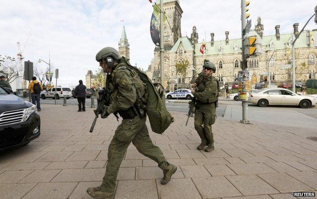 Armed RCMP officers head towards the Langevin Block on Parliament Hill