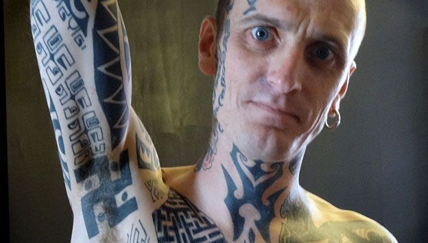 Man (Phil Cummins) showing swastika tattoo