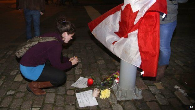 Mourners light a candle and tie a Canadian flag around a light pole near the National War Memorial after a soldier was killed in Ottawa on Wednesday, Oct. 22, 2014
