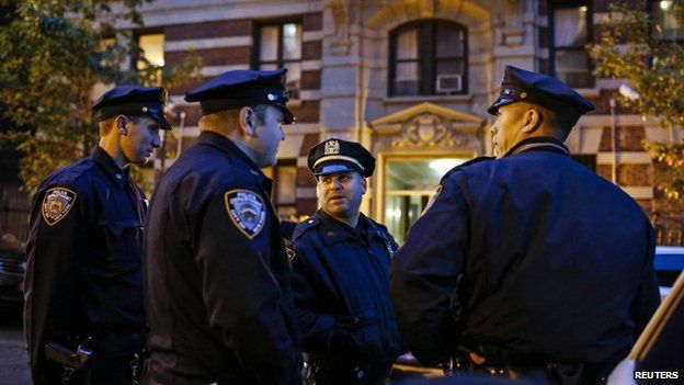 Police officers guard the building where Dr Craig Spencer lives in New York