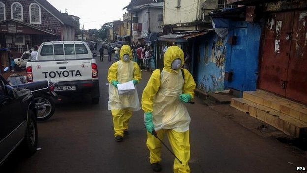 Health workers arrive to pick up the body of a young victim in Freetown, Sierra Leone, 24 Oct