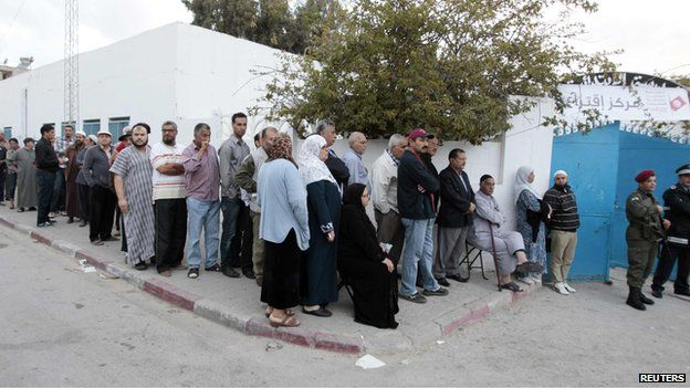 People wait in line outside a polling station to vote in Tunis October 26, 2014