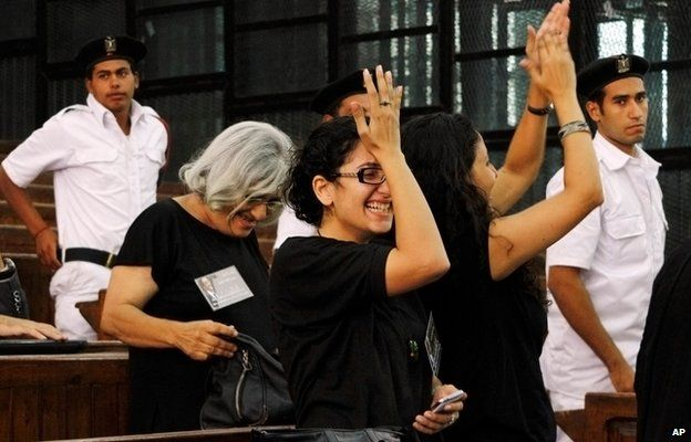 "Prominent Egyptian blogger Alaa Abdel-Fattah""s mother, Laila Soueif, a university professor who is an also an activist, background left, his sisters Sanaa Seif, wearing eyeglasses at center, and Mona Seif, at right, cheer after his release on bail at a courtroom in Cairo, Egypt, Monday, Sept. 15, 2014"