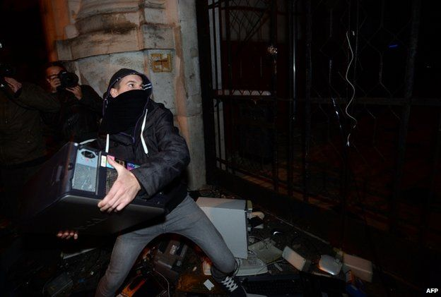 A protester throws the base of an old computer at the headquarters of the Fidesz governor's party in Budapest (26 Oct)
